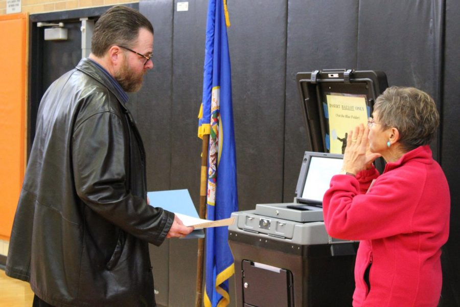 A voter converses with the woman in charge of the ballot scanner Oct. 6. All of Minnesota uses an optical scanner at voting polls.