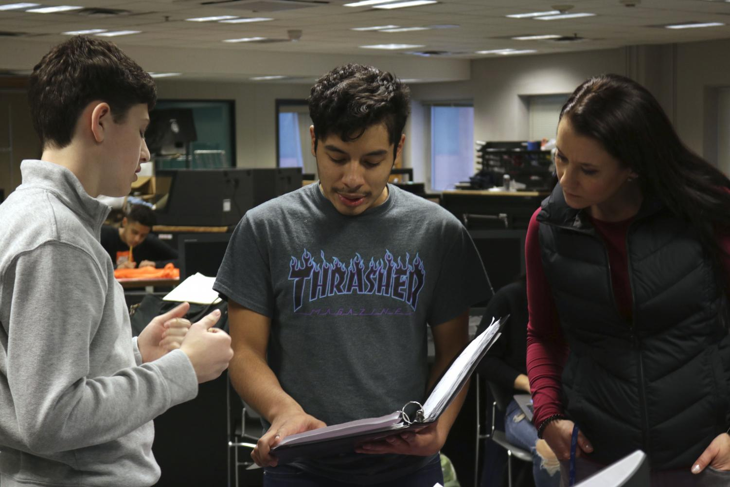 High school students Ethan Meisler and Christian Vega work alongside a professional within the architecture industry on Dec. 13.