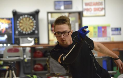 Senior Adam Kowski releases the bowling ball down the lane Dec. 4. Kowski frequently bowls, even during the off season, in order to improve his technique.