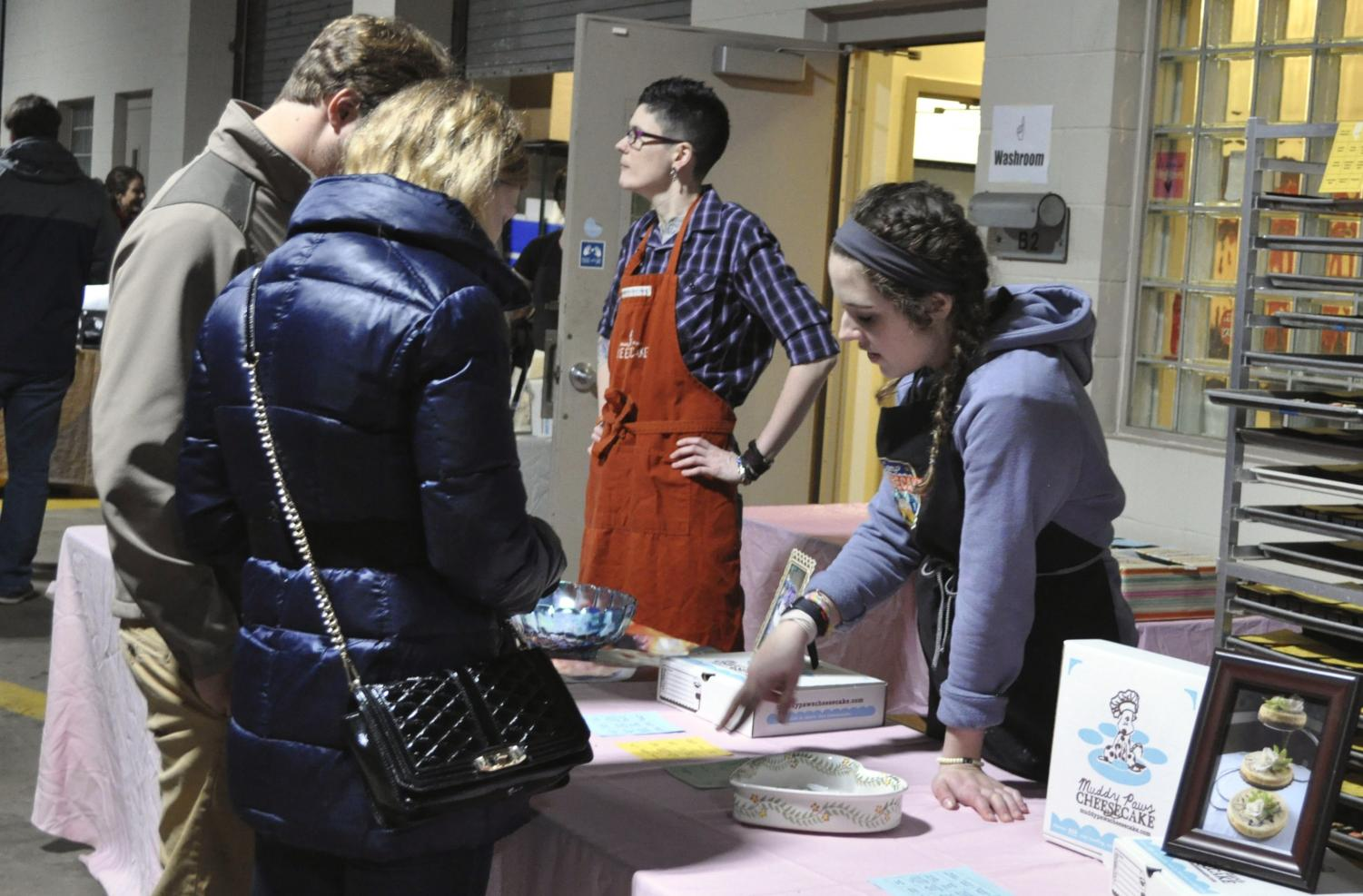 A Muddy Paws Cheesecake employee shows donation participants the different trays available with free samples. Each person who donated a toy or dog food could sample cheesecakes for free.