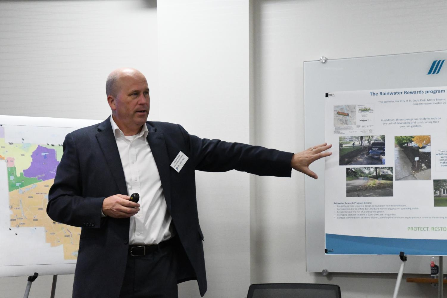 Senior engineering project manager Phillip Elkin talks to community members at the Water Plan meeting. Elkin referenced the poster with information about rain gardens and their effect on the St. Louis Park community as a whole.