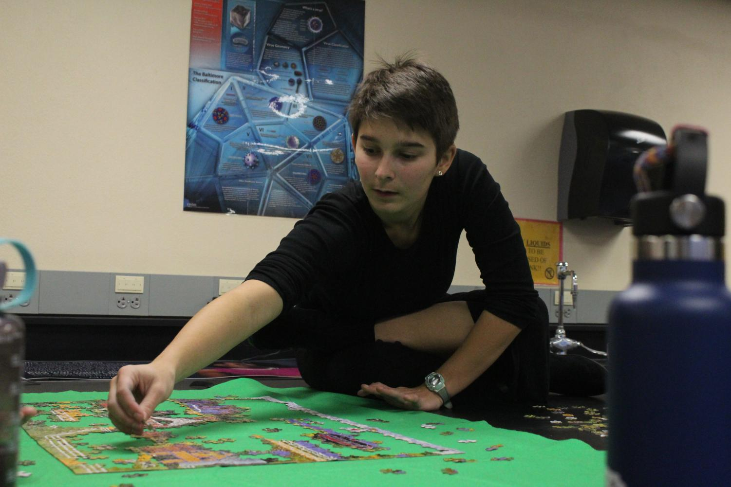 Senior Greta Long sits and laughs on top of a lab table in room A313 alongside her fellow puzzle club members. Long is a co-president of the club with fellow senior Claire Middleton.