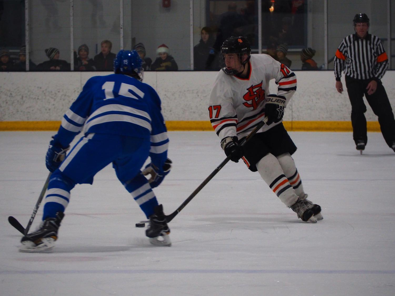 Sophomore Drew Boyum looks for an open player to pass to as sophomore Duke Kiffin attempts to take the puck. Minnetonka beat Park 8-1 December 6.