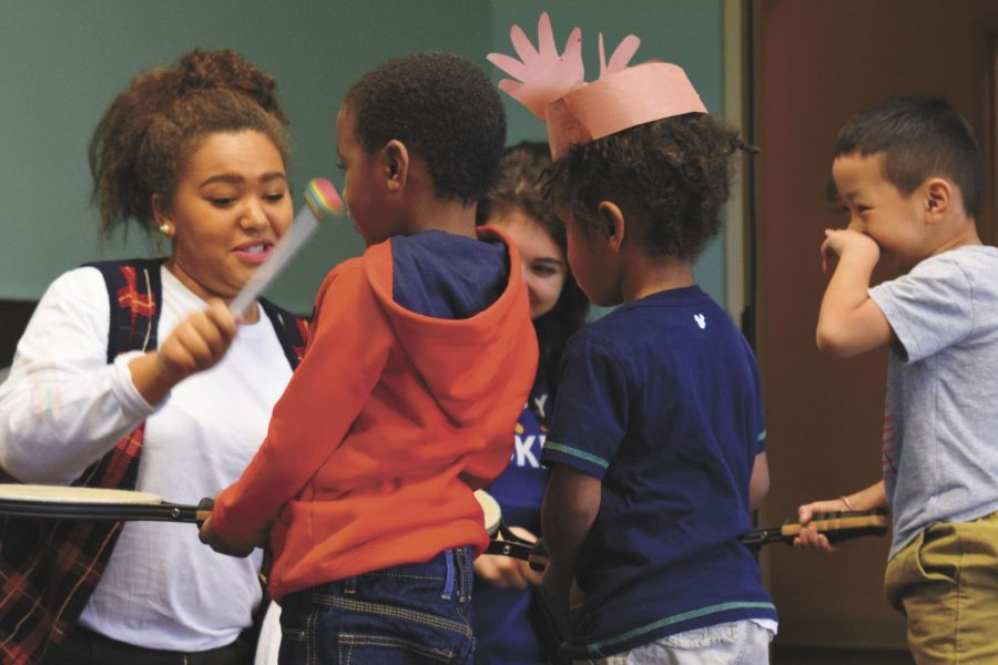 Senior Alexis Machoka volunteers with children during DECAs annual visit to Family Partnership to celebrate the holidays with children in 2016.