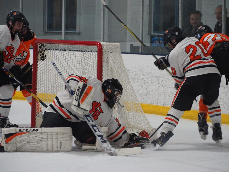 Sophomore Austin Amelse keeps Osseo player off the puck while Junior William Pinney picks it up to save a goal scoring opportunity.