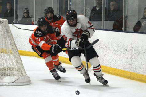 Sophomore McCabe Dvorak swerves around the goal to keep the puck away from two opponents. Park defeated Osseo on Dec. 4 with a final score of 7-3 at the St. Louis Park Rec Center.