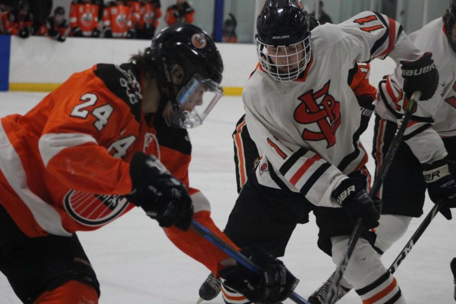 Senior+Tim+Collins+goes+head+to+head+against+rival+Osseo+player+Adam+Larson.+Park+won+their+game+against+Osseo+Dec.+4+at+Park%27s+home+rink%2C+the+Rec+Center.+