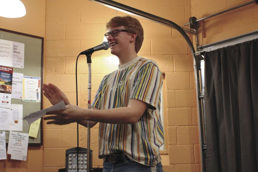 Junior Patrick Djerf announces the next performer at the Nest open mic night Dec. 14. The event was to promote the Nest and showcase students musical talents.