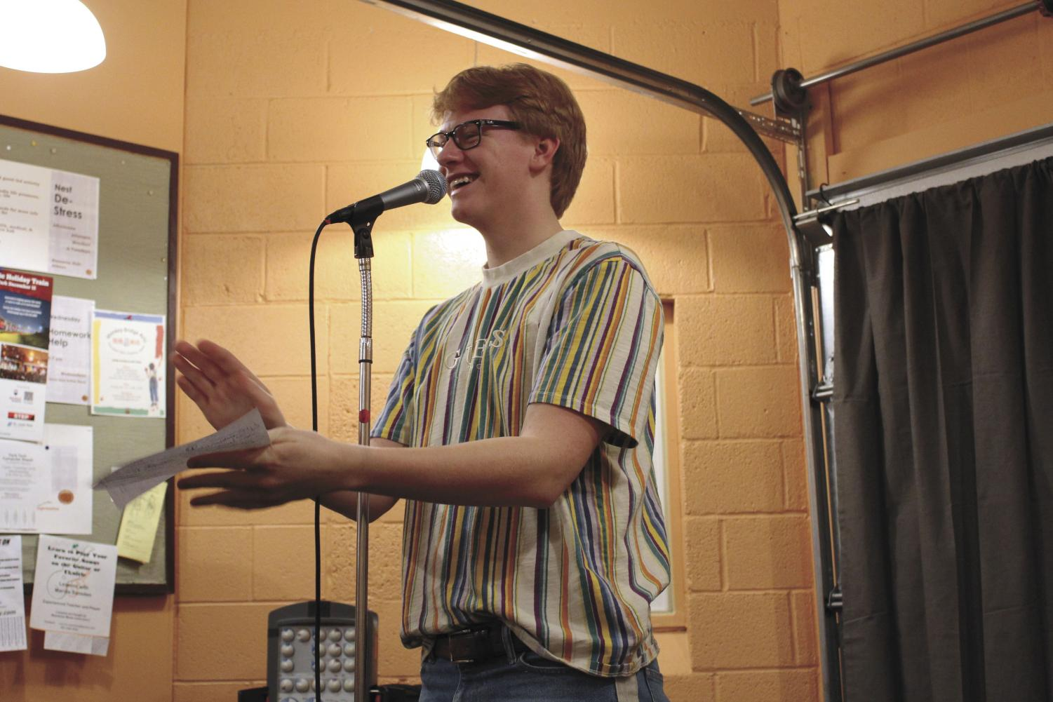 Junior Patrick Djerf announces the next performer at the Nest open mic night Dec. 14. The event was to promote the Nest and showcase student's musical talents.