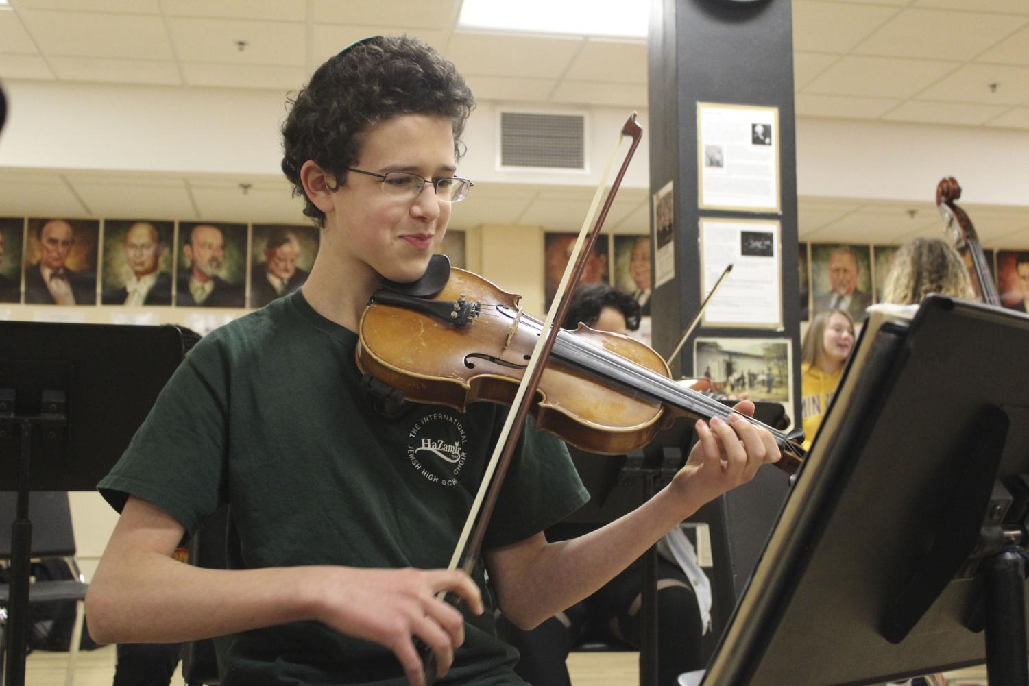 Junior Yoni Potter practices violin during class Dec. 17 in preparation for the orchestra concert Dec. 20.