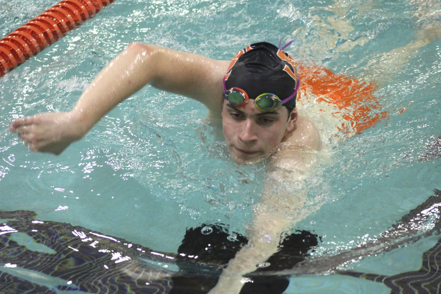 Senior Max Bechtold, practices kicking for the Chaska meet by using a kick board. He swam in the Chaska meet Dec. 13.