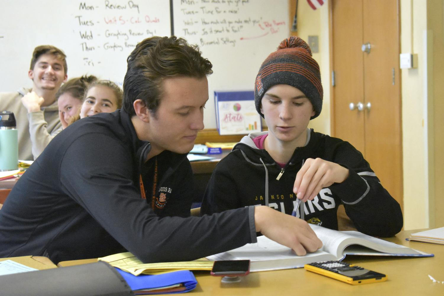 Bobby Otto helps sophomore Elliot Salmon with his math homework. According to Otto, he tries to incorporate the mindfulness aspect of yoga into the classroom because it benefits himself and his students.