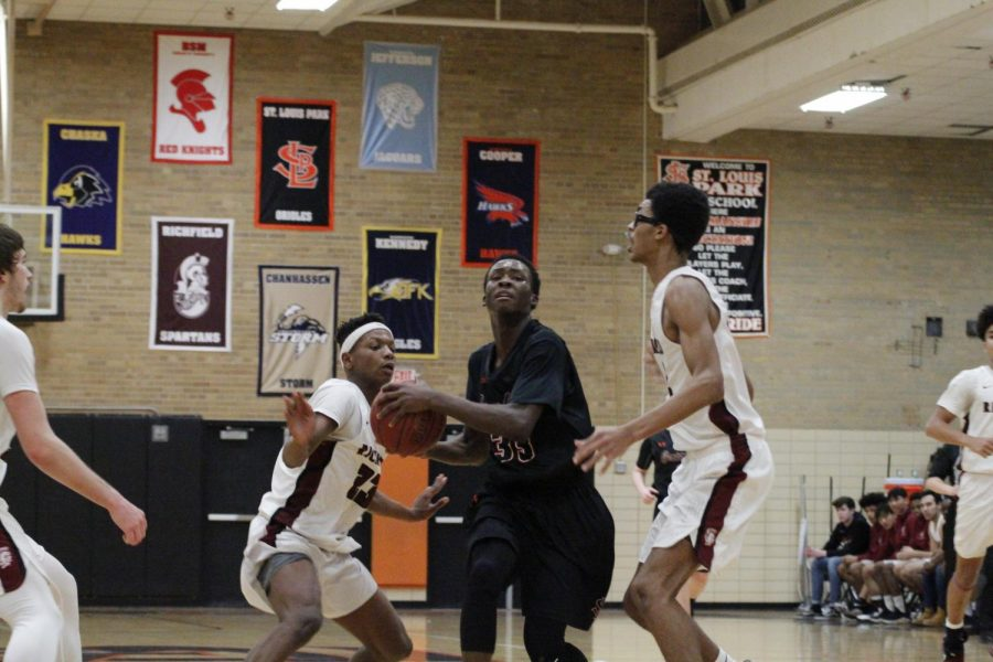 Sophomore+Paris+Johnson+slips+between+two+of+Richfield%27s+defenders+with+the+basketball+in+his+hands.+Park+beat+Richfield+97-79+on+January+17.+Their+next+game+is+against+Benilde-St.+Margaret%27s+at+7+p.m.+Jan.+22+at+Benilde-St.+Margaret%27s+School.