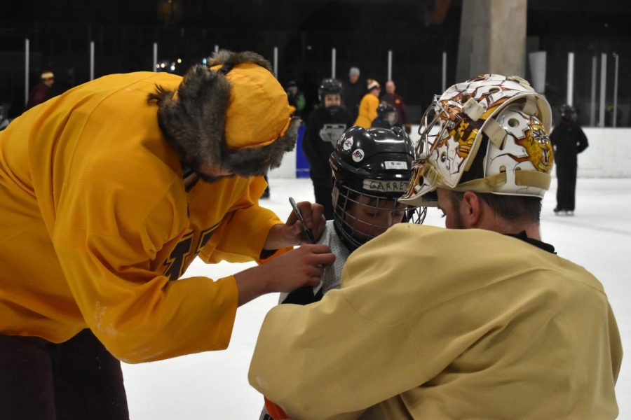 Goalie Brock Kautz and forward Jack Ramsey autograph a young hockey players practice jersey. This event inspires young players to continue to work hard.