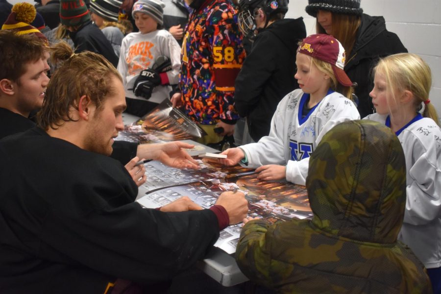 Children+line+up+to+get+autographs+from+Gopher+hockey+players+at+the+%22Gophers+Skate+the+Cities%22+which+was+hosted+at+the+ROC+event+Monday%2C+Jan.+14.+Gopher+player+Tyler+Nanne+signs+a+poster+for+a+young+fan.+The+team+provided+these+posters+and+player+cards+for+all+fans+to+take+home.