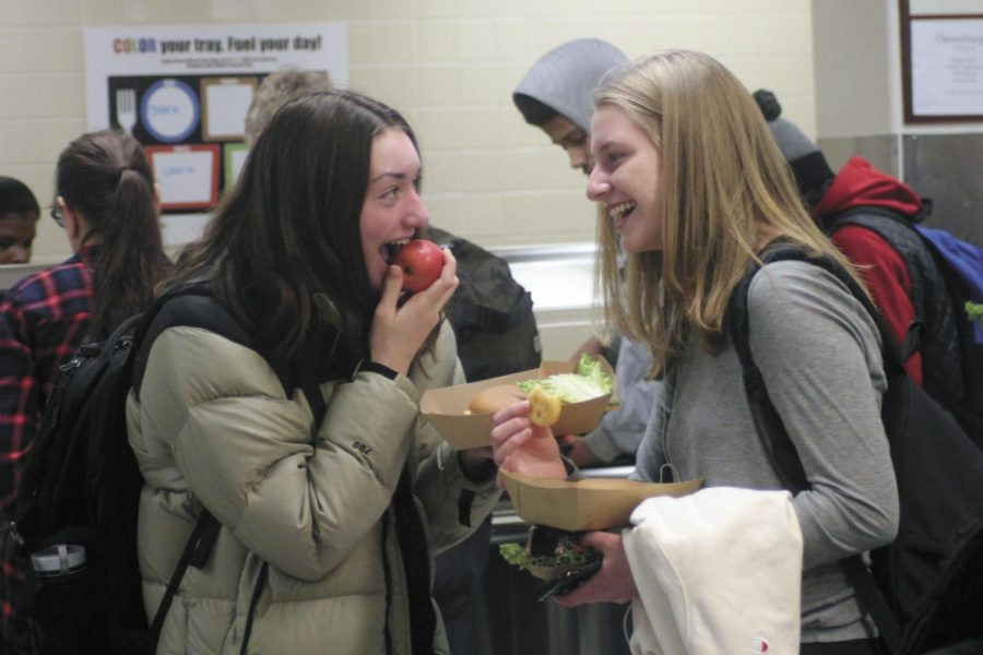 "Switching it up: Sophomores Lily Metzler and Kate Gage laugh after receiving their lunches. Next semester there will be a schedule change in which ""students will see which lunch they have on their schedule, which doesn't really change anything except it'll be on the (physical) schedule,"" Busse said."