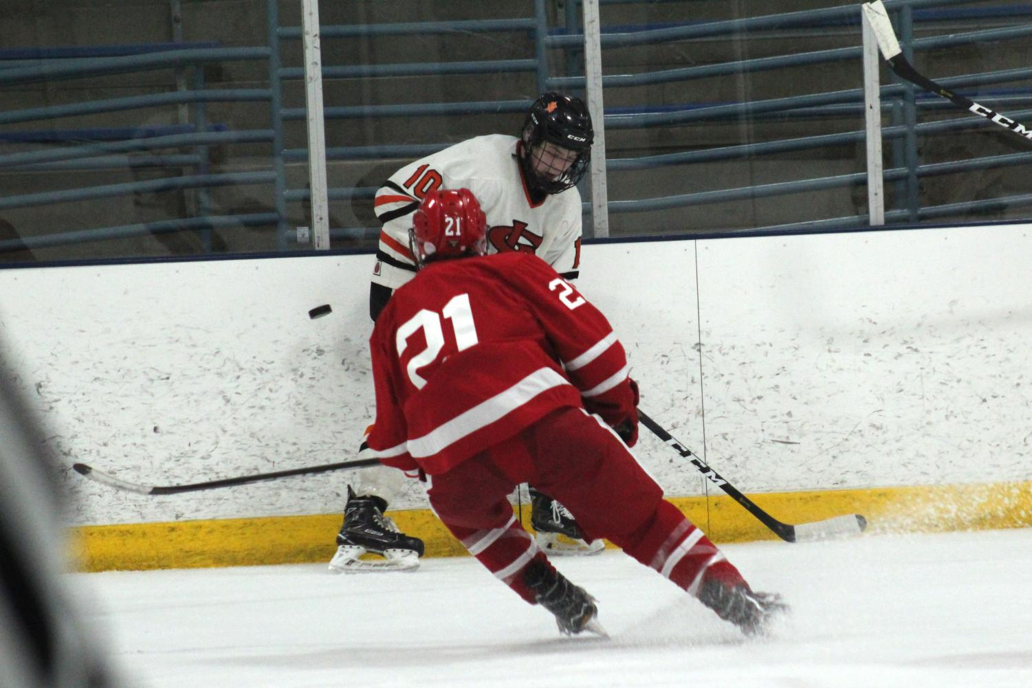 Sophomore Sam Barry attempts to shoot the puck around Benilde's player Blake Mesenburg. The boys' hockey team played Benilde Feb.14 at the Rec center.