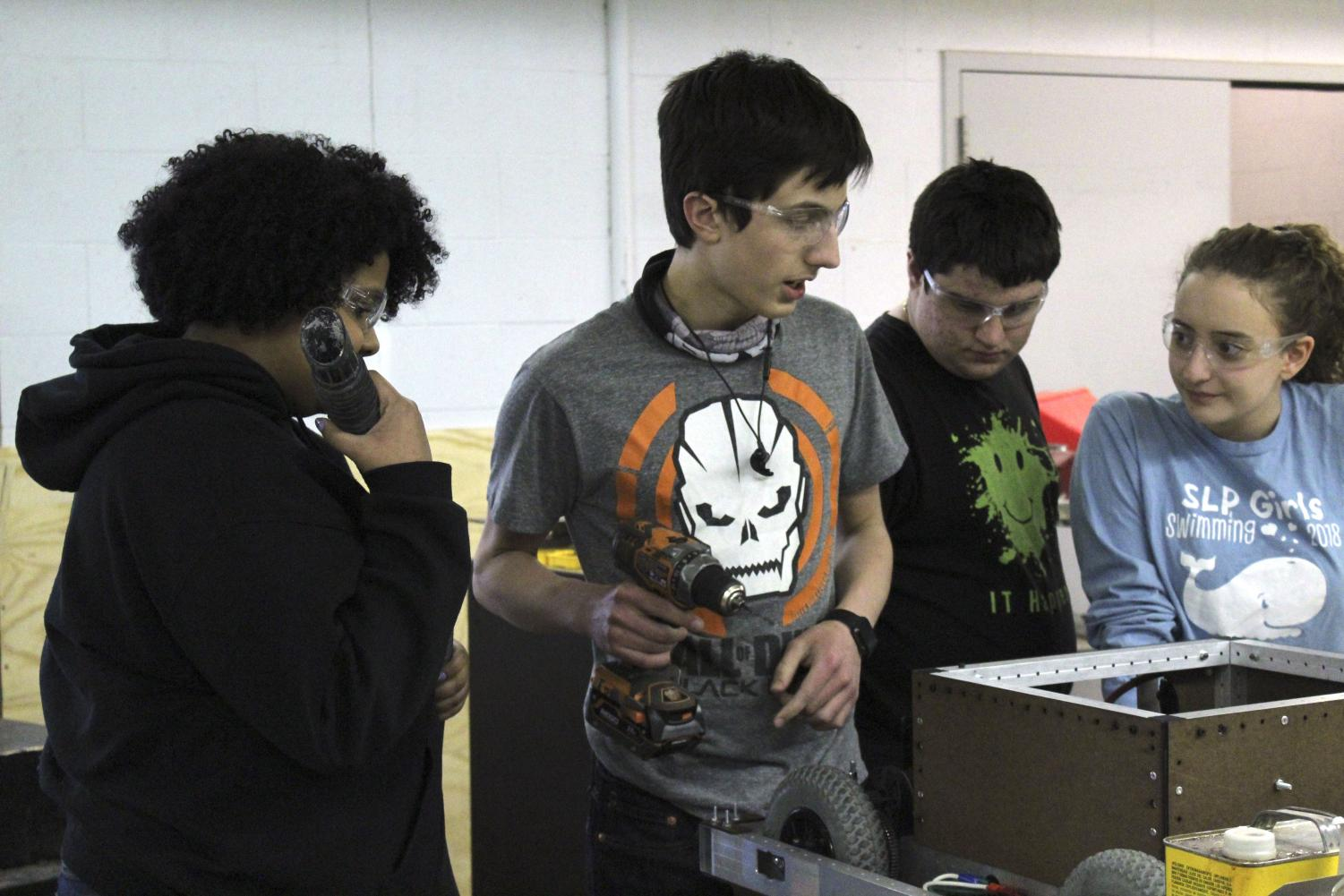 Seniors Serena Moore, Alessandro Giannetti, Anthony David, and sophomore Julia Salita focus on creating their robot for competition Feb. 12. Robotics club will compete on March 29 and 30 at the Williams Arena and Sports Pavillion.