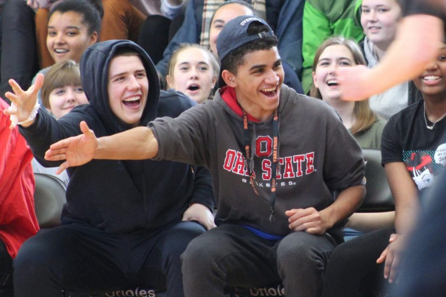 Senior Keyshon Howard and junior Cole Ewald reach to give high fives to students who participated in the student vs. teacher basketball game. The game was to get students pumped up for Sno Daze the following Saturday.