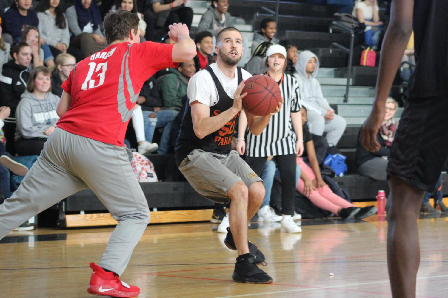 Basketball%2C+Track+and+Cross+Country+coach+Chris+Nordstorm+prepares+to+shoot+the+ball+around+sophomore+Sam+Hunt.+The+teachers+won+for+the+second+time+on+Feb.+15+at+the+second+annual+game.