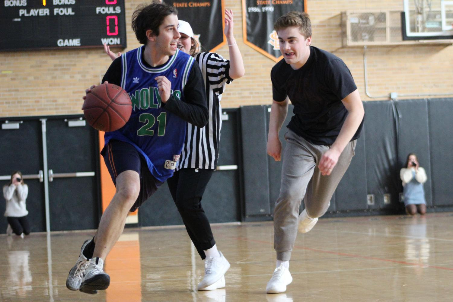 Senior+John+Meyer+dribbles+the+ball+across+the+gym.+During+halftime+three+students+made+an+attempt+at+the+half+court+shot%2C+none+of+them+made+it+in+the+basket.+