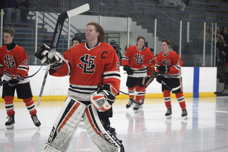 Boys' hockey captain Junior William Pinney skates onto the ice at the beginning of the boys' hockey Senior night.