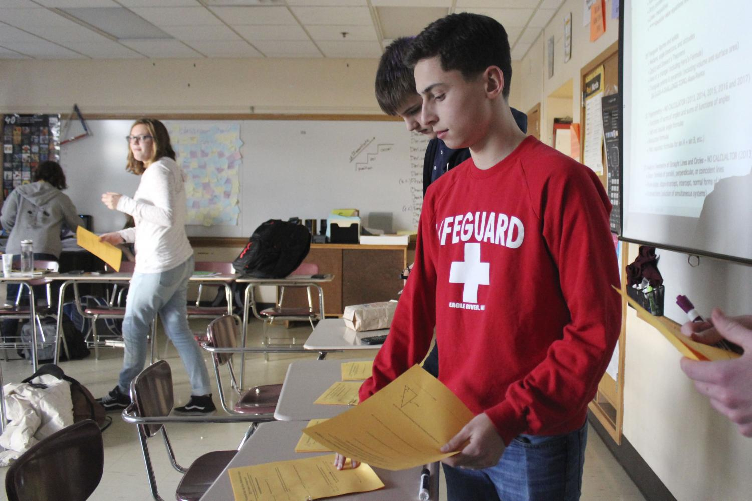 Junior Zachary Weiser collects practice math sheets to complete in Math Club. This meeting Nov. 12 in Ms. Hoesing's room prepared the team for their next competition.