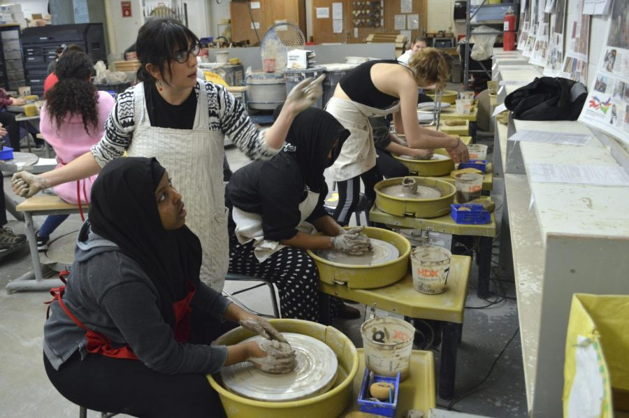 Pottery teacher Angela Jacob assists students while they work with clay during pottery class Feb. 14. According to Jacob, pottery pieces that were not claimed will go to STEPs Empty Bowls.