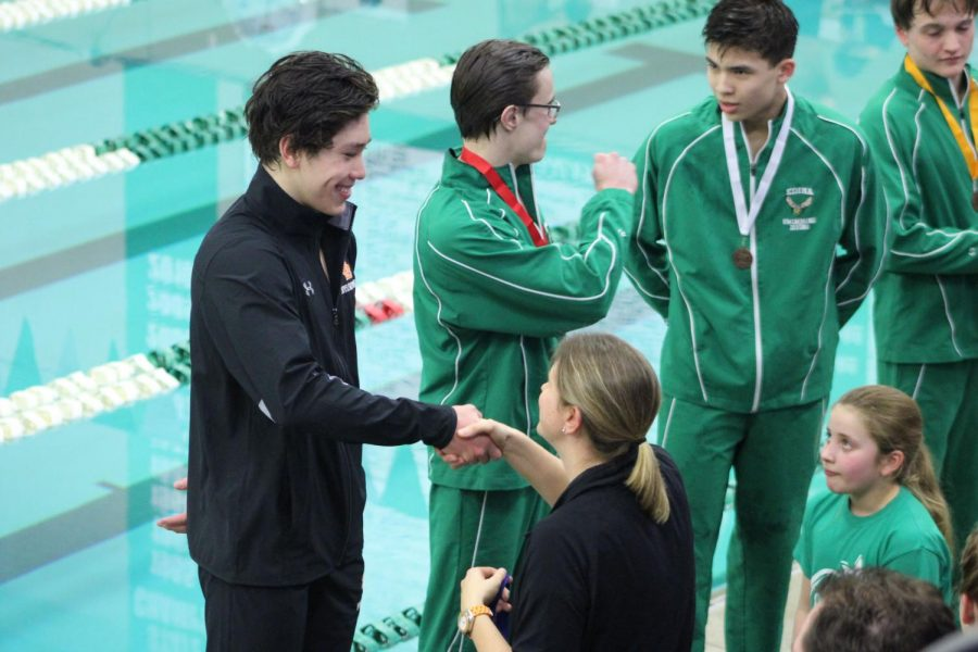 Hayden Zheng accepts first place medal for his performance in the 200 IM. The award was presented to him by math teacher Amanda Forsberg. The time of 1.56.1 minutes and place qualified him for the State meet March 1 and 2.