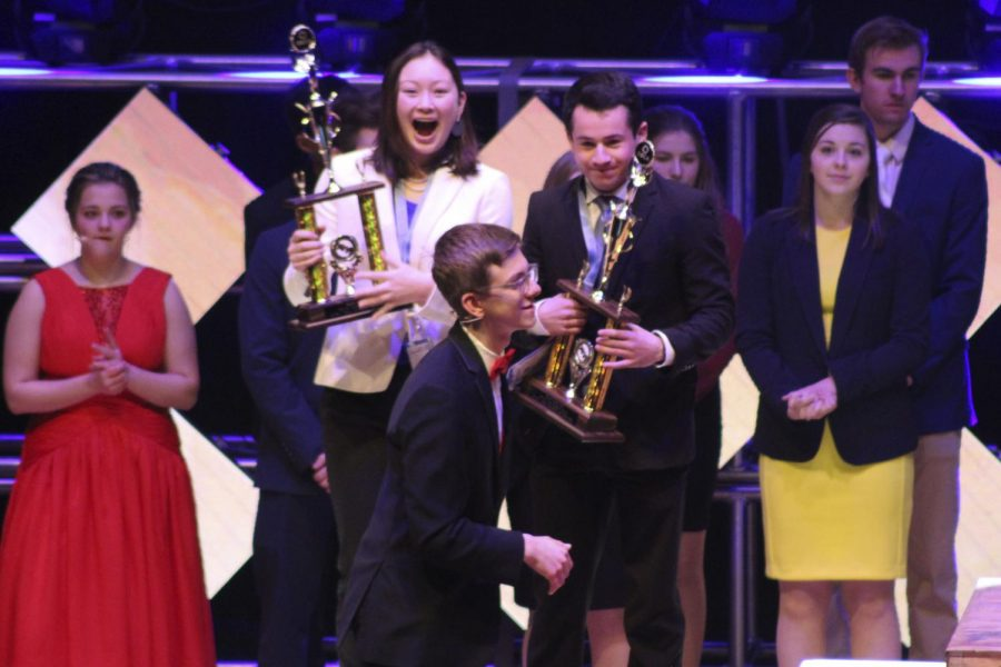 Sophmores+Daniel+Goldenberg+and+Emma+Amon+step+up+to+receive+their+third+place+trophy+for+their+team+decision-making+event+at+the+2019+DECA+State+competition.
