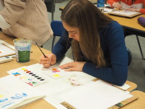 Junior Lauren Schmelzer paints with watercolors in Martha Ortman's painting class March 8. On her own time, Schmelzer takes nature photography and sells her work at the Nest.