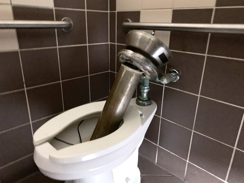A destroyed sink placed in one of the toilets of the boys' bathroom in the B3 hallway March 28. According to Meyers, the district is working on various other projects, which has slowed the repair process for vandalism in the high school bathrooms.