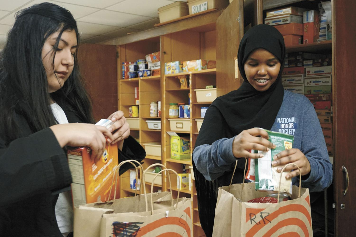 Juniors Victoria Martinez and Mushtakh Mohammad pack bags March 7, for students in need of food. The Birdfeeder is accepting applications for students who rely on school breakfast and lunch and won't have access to food during spring break.