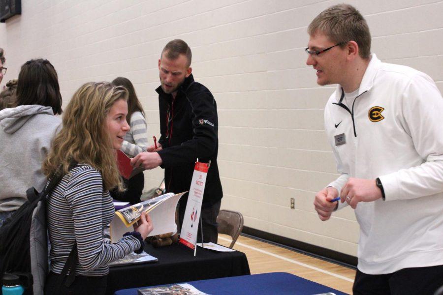 Junior Lola Ruff talks to a representative from a college at the college fair on March 13. The college fair gives students information on colleges they're interested in.