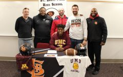 Senior Milkaso Dedefo signs his commitment to play football at the University of Minnesota Crookston on Feb. 6. Dedefo was accompanied by his teammates, coaches, family and friends.