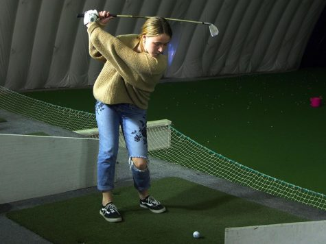 Junior Lily Rostal practices her short game at the Brooklyn Park Golf & Sports Center. Girls' golf had its first practice March 18 and will have its first match at 3:00 p.m. April 8 at Bluff Creek Golf Course.
