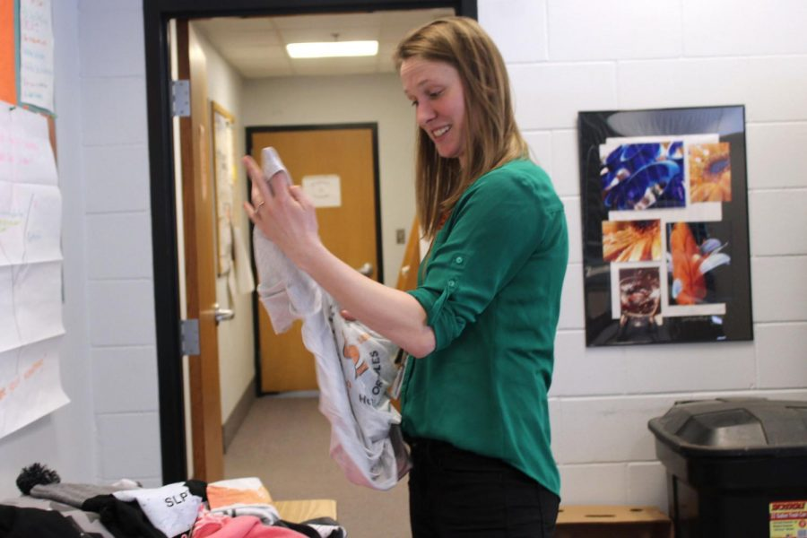 Social studies teacher Jillian Merkle looks at the merchandise to be raffled off laid out in the staff lounge. All of the merchandise is made by a spirit company called Park Prints.