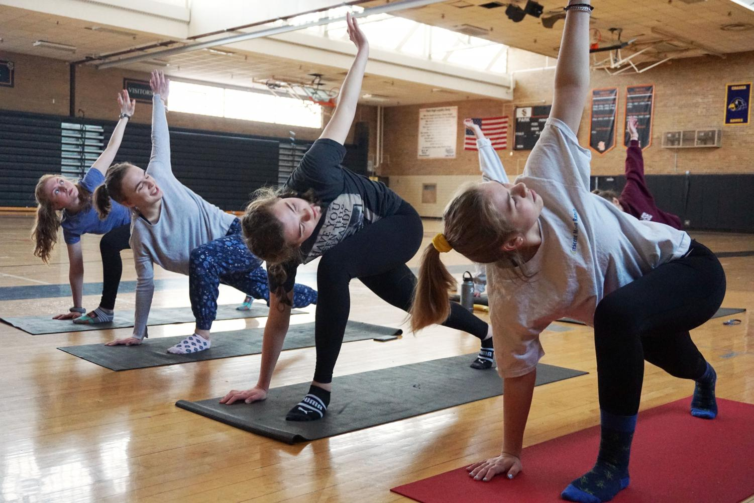 Sophomores Liz Madigan, Elizabeth Orton, Keely Berntsen and Mimi Kniser participate in yoga club before school March 28 as a way to destress before the hectic school day. The club meets every Thursday morning before school in the old gym and is led by math teacher, Bobby Otto.