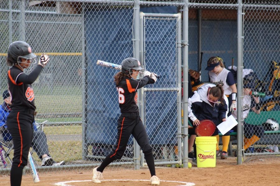Junior Caitlin Seaman practices her swing while waiting to hit next. Seaman is the second person to bat on her team. Senior Madison Mclntosh hits first.
