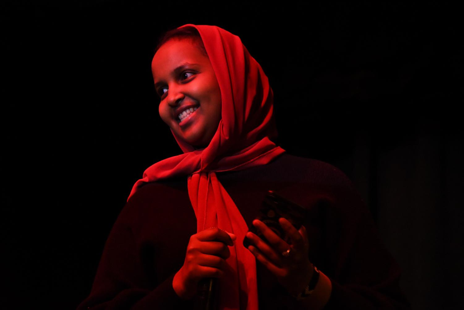 Senior Muna Ahmed smiles while the crowd applauds her after reading a poem during the multicultural show, April 12. During the show, students performed in a variety of different mediums such as song, rap, dance and spoken word.