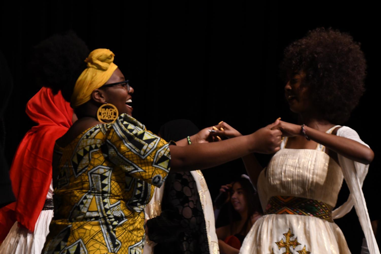 Senior Aisha Abdi and sophomore Grace Kanyinku celebrate after the final performance.