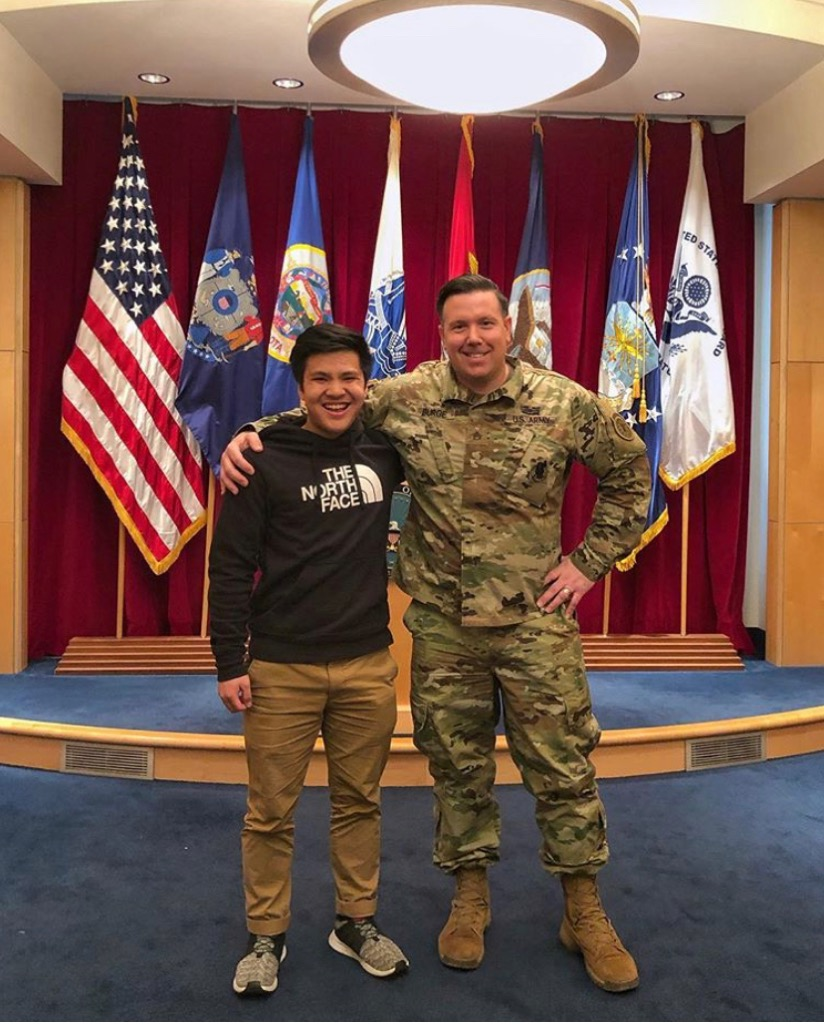 Senior Bryan Huynh poses with an United States Army personal after making his commitment.