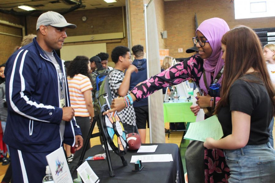 Freshmen Maya Frank and Isra Mohamed spin a wheel at the Pros of the Rope booth to win a prize. The founder of Pros of the Rope Jon Reese interacted with Park students at the career fair April 24.