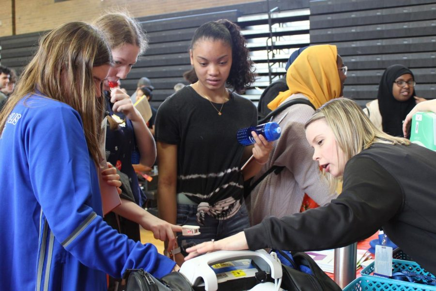 Freshmen Maree Lasala and Caroline Butler test their oxygen levels with a representative from the Hennepin County Medical Center at the career fair. The medical center's booth also included an emergency medical technician that spoke to students about her career.