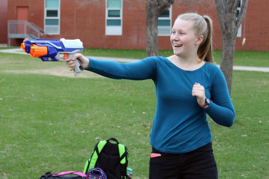 Junior Ellen Poulter practices aiming her Nerf gun with her teammates April 24. Her team purchased new zombie bullets to improve the distance of its shots.