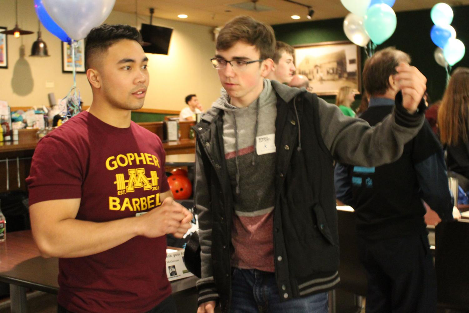 Junior Brandon Wetterlin discusses with a fellow volunteer about their bowling team's performance during the Bowl-A-Thon April 13 at Park Tavern. This was the 27th annal Bowl-A-Thon for Reach for Resources.