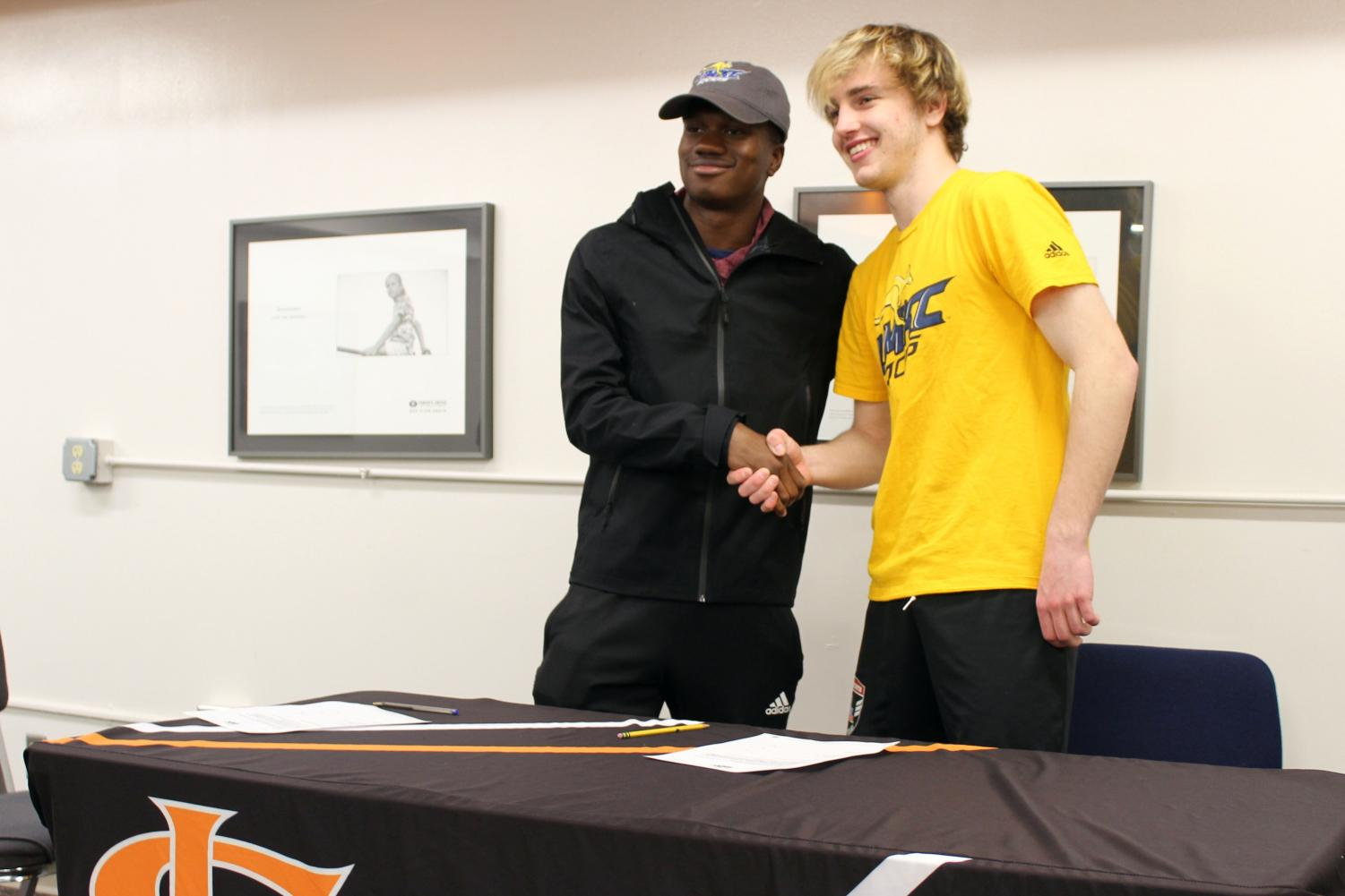 Seniors Emmanuel Iwe and Zinedine Kroeten shake hands after signing to play soccer for University of Missouri Kansas City, April 21. They began playing together at the soccer club Joy of the People.