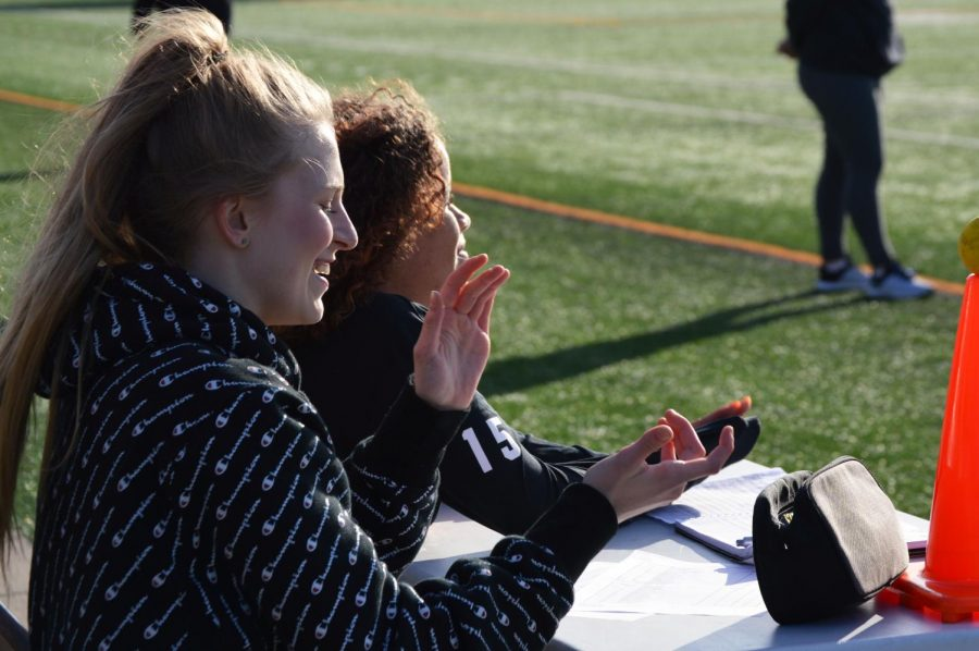 Junior Ella Thomas supports the girls' lacrosse team during its game April 26. Team managers do various jobs to help the team, including keeping score of games and providing assistance to the coach.