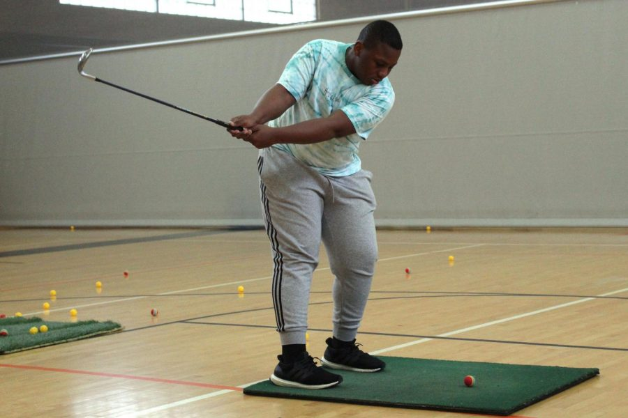 Sophomore Michael Boxley practices his swing at practice April 15. The boys' golf team practiced inside the school gym because of bad weather.