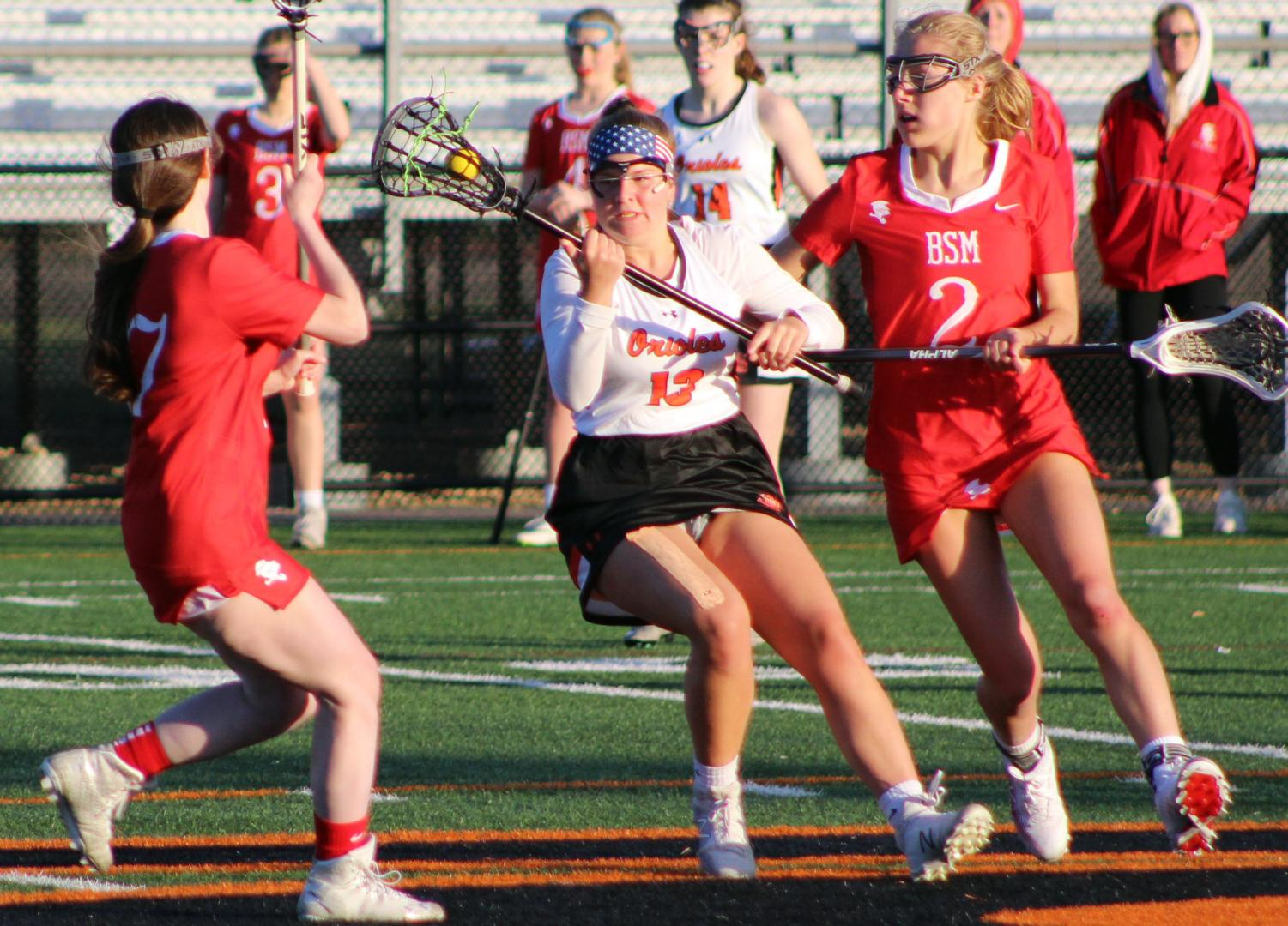 Junior Anna Nicholls cradles the ball to move between two Benilde-St. Margaret players April 18. Park's next game is against Hopkins 6 p.m. April 23 at the stadium.